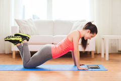 Smiling teenage girl doing push-ups at home Stock Photography