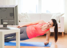 Smiling teenage girl doing side plank at home. Fitness, home and diet concept - smiling teenage girl doing side plank and watching tv at home stock photography