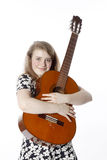 Smiling teenage girl in dress holds guitar in studio stock photography