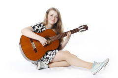 Smiling teenage girl in dress plays the guitar sitting on the f Royalty Free Stock Images