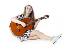 Smiling teenage girl in dress plays the guitar sitting on the fl. Oor in studio with white background stock image