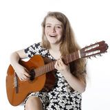 Smiling teenage girl in dress plays the guitar in studio Stock Photos