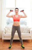 Smiling teenage girl exercising with dumbbells Stock Photos