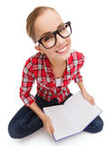 Smiling teenage girl in eyeglasses reading book Royalty Free Stock Photos