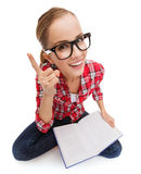 Smiling teenage girl in eyeglasses reading book Stock Image
