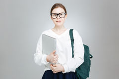 Smiling teenage girl in glasses holding green backpack and laptop Royalty Free Stock Photo