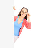 Smiling teenage girl with glasses standing behind blank panel Royalty Free Stock Photos