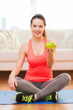 Smiling teenage girl with green apple at home Stock Images
