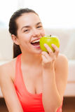 Smiling teenage girl with green apple at home Royalty Free Stock Image