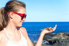 Smiling teenage girl holding an atlantic crab on ocean coast. Teenage funny smiling girl in red sunglasses holding an atlantic crab on ocean coast. Blue Royalty Free Stock Photo