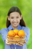 Smiling teenage girl holding basket of oranges Stock Photo
