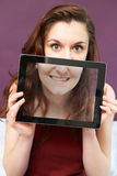 Smiling Teenage Girl Holding Digital Tablet In Front Of Face. Teenage Girl Holding Digital Tablet In Front Of Face stock photo