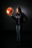 Smiling teenage girl holding orange fireball. Smiling teenage girl in black jacket holding orange fireball stock images