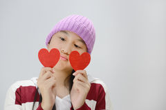 Smiling teenage girl holding red paper hearts over grey background Stock Image