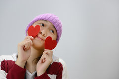 Smiling teenage girl holding red paper hearts over grey background Stock Images