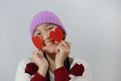 Smiling teenage girl holding red paper hearts over grey background Royalty Free Stock Images