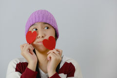 Smiling teenage girl holding red paper hearts over grey background Stock Photos