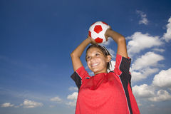 Smiling teenage girl holding soccer ball overhead Royalty Free Stock Images