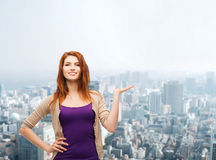 Smiling teenage girl holding something on her palm Royalty Free Stock Images