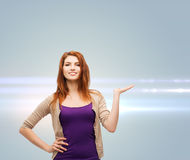 Smiling teenage girl holding something on her palm Royalty Free Stock Photo