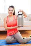 Smiling teenage girl with jar of protein at home Stock Image