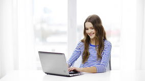 Smiling teenage girl with laptop computer at home stock footage