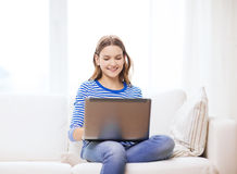 Smiling teenage girl with laptop computer at home Royalty Free Stock Image