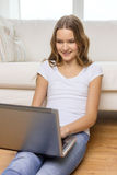Smiling teenage girl with laptop computer at home Royalty Free Stock Images