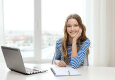 Smiling teenage girl laptop computer and notebook Royalty Free Stock Photography