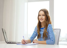 Smiling teenage girl laptop computer and notebook Royalty Free Stock Image