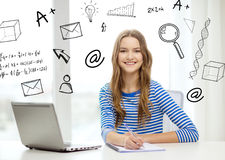 Smiling teenage girl laptop computer and notebook. Education, technology and home concept - smiling teenage girl with laptop computer, notebook and pen at home stock image