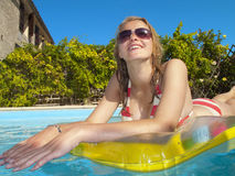 Smiling teenage girl laying on pool raft and looking up in swimming pool Stock Image