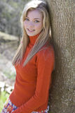 Smiling teenage girl leaning against tree stock images