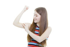 Smiling teenage girl measures her biceps Royalty Free Stock Image