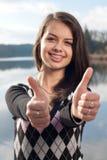 Smiling teenage girl picks up big thumbs up Stock Image