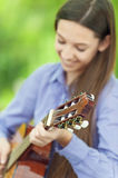 Smiling teenage girl playing guitar Royalty Free Stock Photography