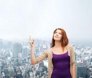 Smiling teenage girl pointing finger up Stock Photos