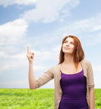 Smiling teenage girl pointing finger up Stock Photo
