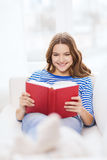 Smiling teenage girl reading book on couch Stock Images