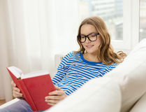 Smiling teenage girl reading book on couch Stock Photography