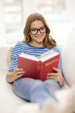 Smiling teenage girl reading book on couch Royalty Free Stock Photography
