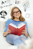 Smiling teenage girl reading book on couch Stock Photos