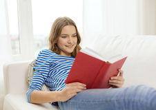 Smiling teenage girl reading book on couch Royalty Free Stock Photos