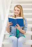Smiling teenage girl reading book Royalty Free Stock Photography