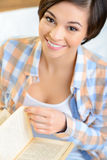 Smiling teenage girl is reading a book Stock Photos
