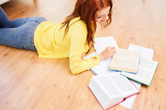 Smiling teenage girl reading books on floor Royalty Free Stock Photos