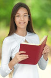 Smiling teenage girl reading red Royalty Free Stock Photography