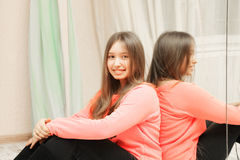 Smiling teenage girl at mirror Stock Photo