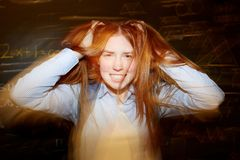 Funny student. Smiling teenage girl ruffling her long ginger hair with hands and having fun Royalty Free Stock Images