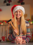 Smiling teenage girl in santa hat with hammer and piggy bank Stock Photos